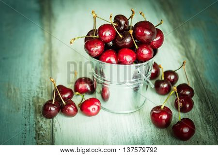 Cherries in a small metal bucket on a wood background
