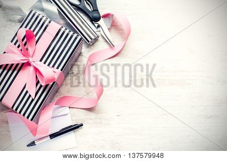 Gift box wrapped in black and white striped paper with pink ribbon and wrapping materials on a white wood old background. Vintage style.