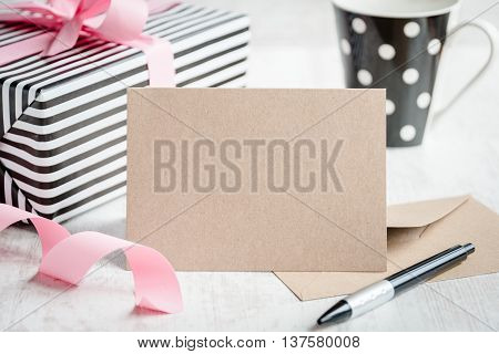 Empty greeting kraft card. Wrapped gift and coffee cup in the background.