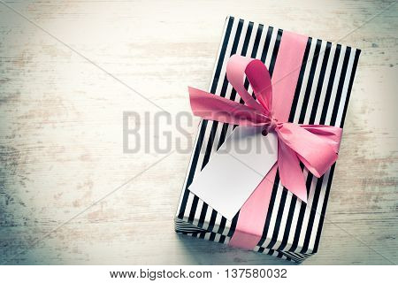 Gift box wrapped in black and white striped paper with pink ribbon on a white wood old background. Empty note tied over. Vintage style.