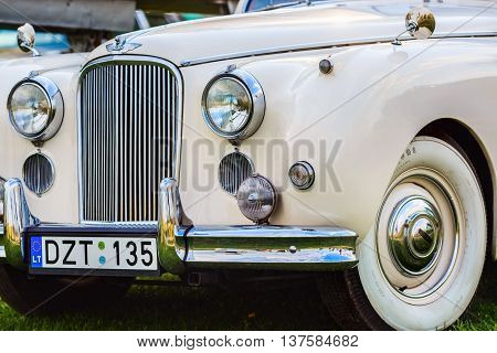 MINSK BELARUS - MAY 07 2016: Close-up of white Jaguar Mk VIII. This classic car was produced in the years 1956-1958. Front part of an vintage retro auto. Selective focus on the car's headlight.