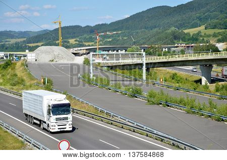 Dolny Hricov, Slovakia - June 29, 2016: White MAN truck drives on slovak D1 highway. In background is new part of this way under construction.