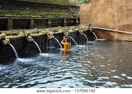 BALI, INDONESIA, 26 MAY, 2015: A woman bathing and praying in the fountain of holy water of Tirta Empul Temple in Bali Indonesia
