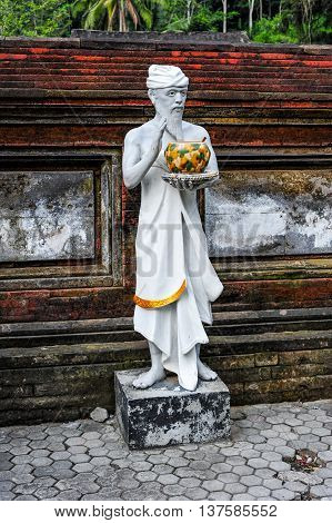 BALI, INDONESIA, 26 MAY, 2015: Sculpture of a priest holding a can of Holy Water in Tirta Embul temple of Bali Indonesia