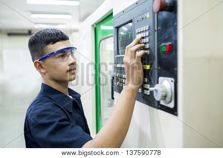 Technician controlling CNC machine.Man input program by keyboard.