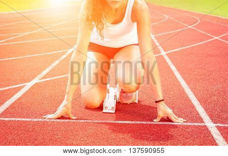 Runner woman at start line on red athletic track - Cropped girl sprinter athlete kneeling on starting block with sunrise lights background - Concept of human concentration -