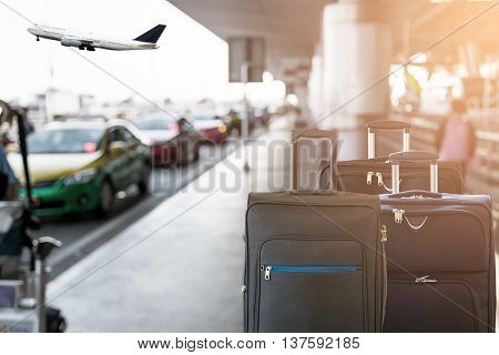 Closeup of group of luggage with the blurred of the taxi park at the airport terminal background. poster