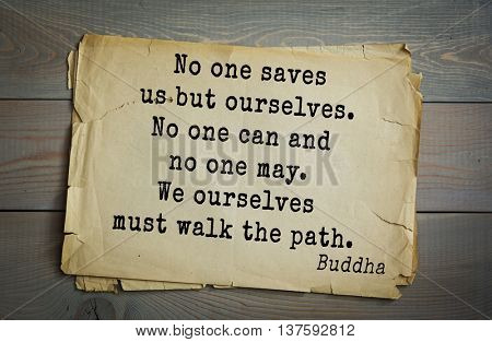 Buddha quote on old paper background. No one saves us but ourselves. No one can and no one may. We ourselves must walk the path.