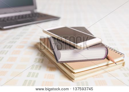 Smartphone on top of books with out of focus computer laptop in background all on bed with soft lighting and selective focus