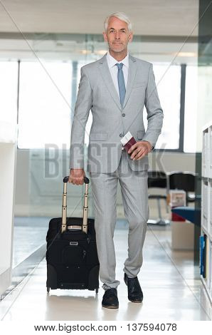 Senior businessman walking with suitcase and holding flight ticket and passport in airport. Business traveler at international airport walking to terminal gate for airplane travel trip.