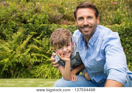 Portrait of happy dad and child looking at camera. Smiling father sitting with child in the park. Father embracing son in the garden.