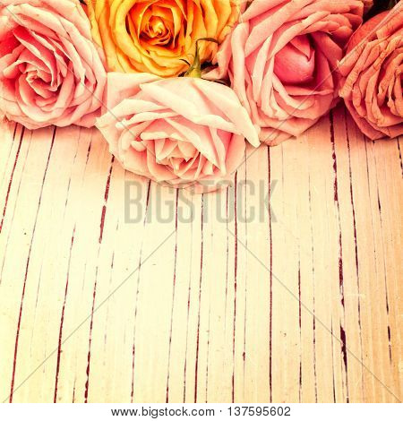Vintage retro background with roses on wooden table