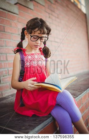 Girl reading a book outside on a sunny day