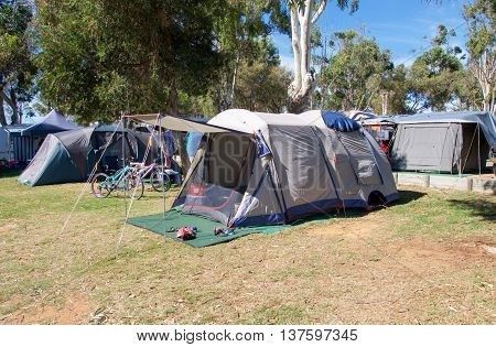 Dome tents in outdoor campground with green trees in Kalbarri, Western Australia.
