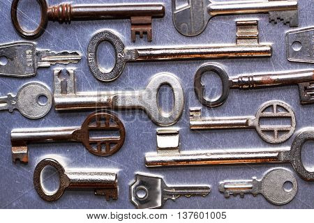 Various old house keys against metal background