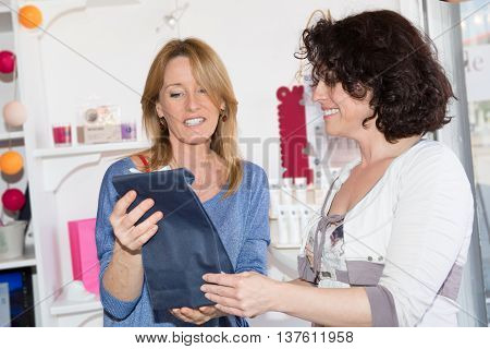 Woman Comparing Cosmetics Products With Saleswoman In A Drugstore