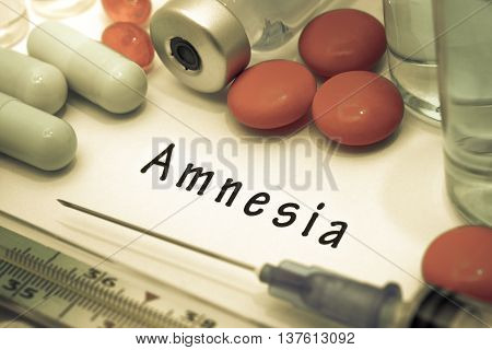 Amnesia - diagnosis written on a white piece of paper. Syringe and vaccine with drugs.