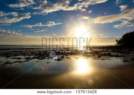 Sunrise over the ocean from a beach with bright glow