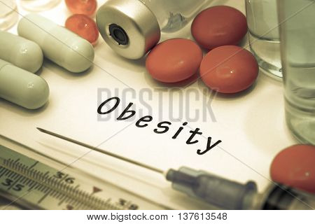 Obesity - diagnosis written on a white piece of paper. Syringe and vaccine with drugs.