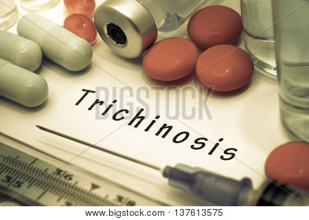 Trichinosis - diagnosis written on a white piece of paper. Syringe and vaccine with drugs