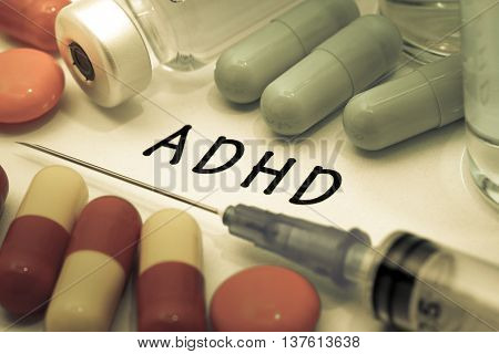 ADHD - diagnosis written on a white piece of paper. Syringe and vaccine with drugs