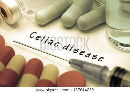 Celiac disease - diagnosis written on a white piece of paper. Syringe and vaccine with drugs.