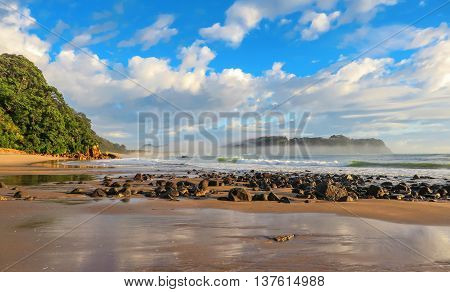 Beach with rocks and mist over the ocean