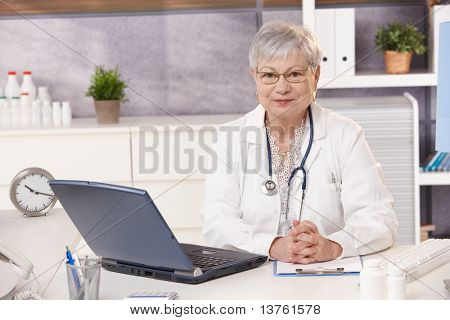 Portrait of senior doctor at work, looking at camera, sitting at desk.?