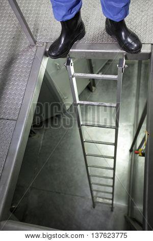 Legs in galoshes at metal ladder