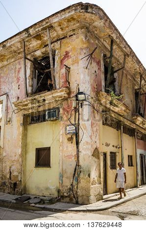 HAVANA - CUBA JUNE 19, 2016: Man walks by one of the many crumbling buildings at the corner of Calle Inquisidor in the La Habana Vieja neighborhood