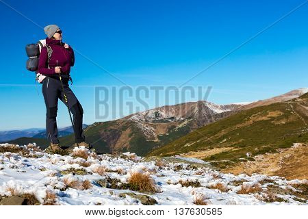 Energetic Female Hiker Staying on Snowy Terrain and Observing Scenic Mountain View Sporty Clothing Jacket and Pants Backpack and Walking Pole