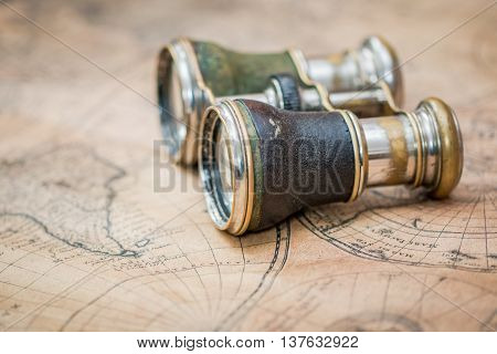 Travel concept with binoculars on an antique map