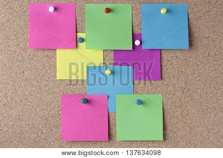 background of colored notes with colored push pins on a cork pinboard