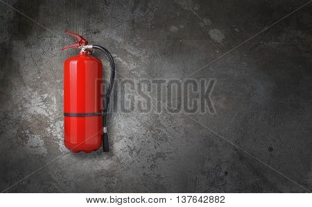 fire extinguisher on a grunge gray wall