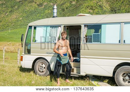 Tora,New Zealand -November 27,2011; Traveling alone in mobile home surfer stands by door to his converted bus with wetsuit pulled down to waist after morning surf.