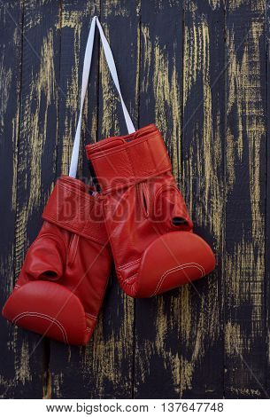 red boxing gloves hanging on a nail on a black wooden wall