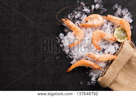 Fresh shrimp with lemon on ice in brown burlap bag on black table top view. Culinary seafood eating.