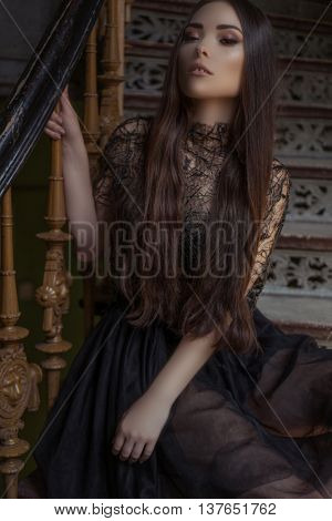 Beauty fashion woman with long hair and smokey eyes , sitting on the stair case  wearing designer stylish dress