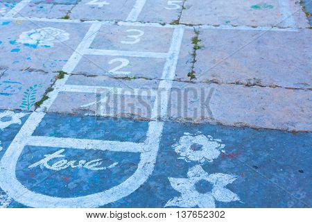 Hopscotch On An Asphalt Floor With Chalk Drawings Of Numbers And Squares