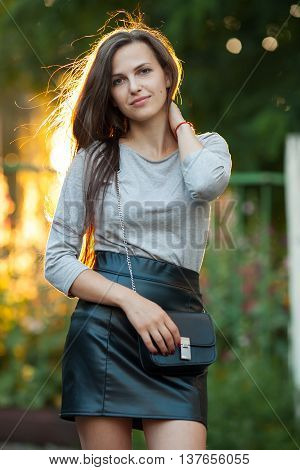 Young Beautiful Brunette Woman In Grey Blouse Black Leather Skirt And Clutch Standing In Sunlight To