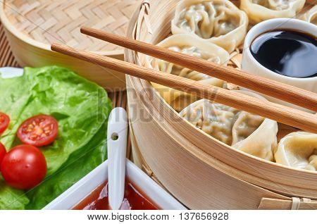 Steamed asian dumplings. Dumplings with fillings in a bamboo steamer