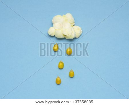 Creative concept photo of popcorn with seeds falling down on blue background.