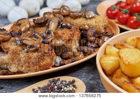 Pork roulades with mushrooms and vegetables on a rustic table