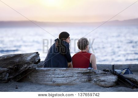 Young multiracial couple sitting on driftwood log talking on beach at sunset. Diveristy multiethnic relationship.