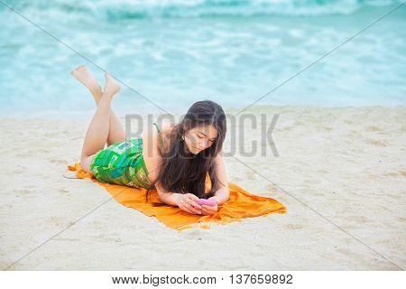 Beautiful biracial Asian Caucasian teen girl lying on tropical beach with cell phone