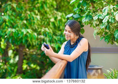 Beautiful biracial Asian Caucasian teen girl using cellphone outdoors by railing