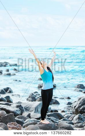 Slim fit biracial Christian teen or young woman standing on rocks by ocean in Hawaii lifting arms in praise with blue waves in background