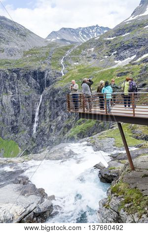 GERANGERFJORD, NORWAY - JUNE 29: Tourists on a viewing platform near the Trollstigen road between the mountains on June 29, 2016 in Geiranger, Norway. Geirangerfjord is UNESCO heritage site.