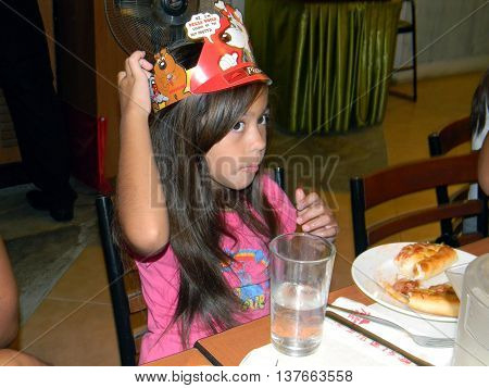 CEBU CITY, CEBU / PHILIPPINES - AUGUST 12, 2011: A girl eating pizza at the Pizza Hut in the SM City Cebu shopping mall adjusts her crown.
