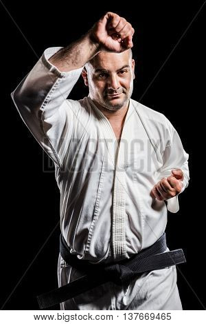 Portrait of fighter performing karate stance on black background